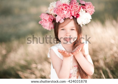 Smiling baby girl 4-5 year old posing outdoors, wearing peony wreath. Looking at camera. Childhood.  - stock photo