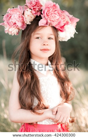 Smiling baby girl 4-5 year old posing with peony wreath outdoors. Looking at camera. Summer season.
