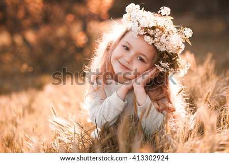 Smiling baby girl 3-4 year old wearing flower wreath outdoors. Sitting in meadow. Looking at camera. Childhood.  - stock photo