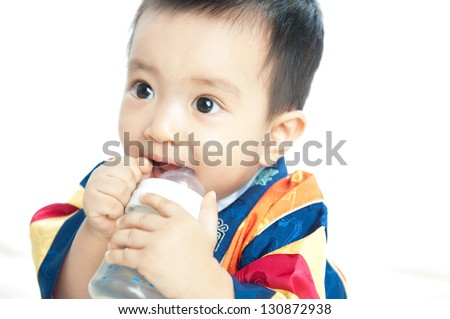 Smiling baby holding and suckling milk bottle