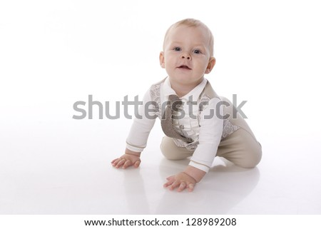 Smiling baby in a beige romper suit and tie crawling. On a white background with reflection