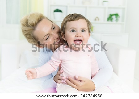 Smiling baby little girl in mom's arms  looking at camera.Shallow doff