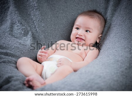 smiling baby looking at camera lying on blanket/towel