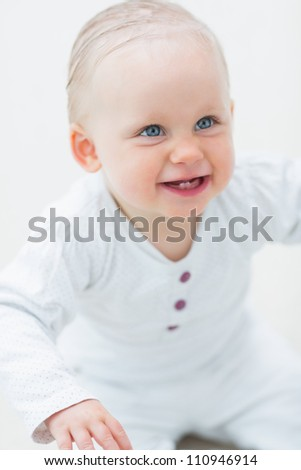Smiling baby looking up in living room - stock photo