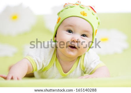smiling baby lying on green - stock photo