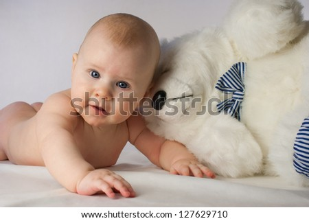 Smiling baby on white background with toy - stock photo