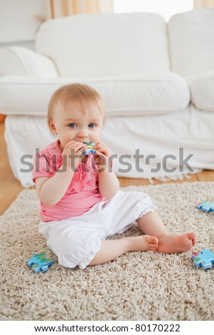 Smiling baby playing with puzzle pieces while sitting on a carpet in the living room - stock photo