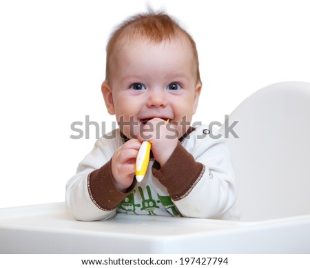 Smiling baby sits on chair with spoon in his hands - stock photo