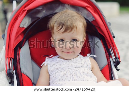 smiling baby sitting in comfortable red stroller