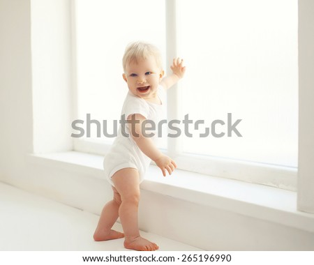 Smiling baby standing in white room at home near window - stock photo