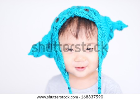 smiling baby wearing blue cap  - stock photo