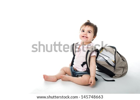 Smiling baby with a backpack full of books