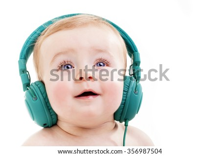 Smiling baby with headphones listening to music, isolated on white background - stock photo