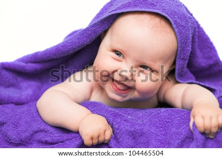 Smiling baby with towel - stock photo
