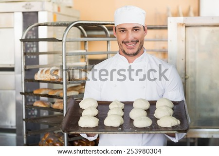 Smiling baker holding tray of raw dough in the kitchen of the bakery - stock photo