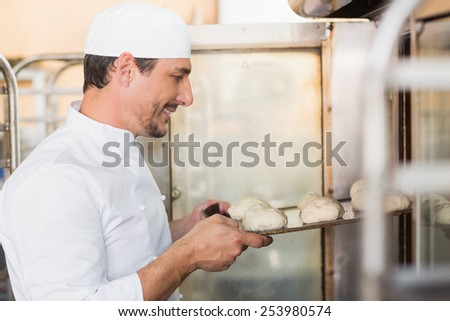 Smiling baker putting dough in oven in the kitchen of the bakery - stock photo