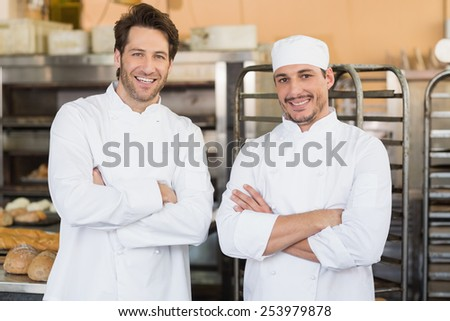 Smiling bakers looking at camera in the kitchen of the bakery - stock photo