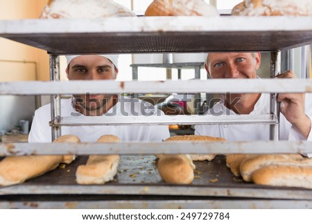 Smiling bakers looking through tray of bread in the kitchen of the bakery - stock photo