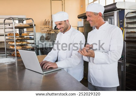 Smiling bakers working together on laptop in the kitchen of the bakery - stock photo