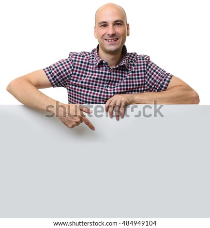 smiling bald Man pointing at blank poster