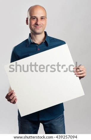 smiling bald man presenting empty paper sheet. Isolated on gray - stock photo