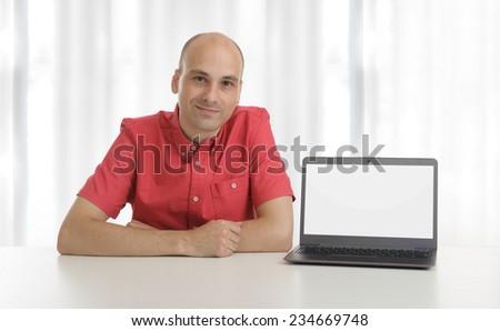 smiling bald man presenting something on screen of laptop - stock photo