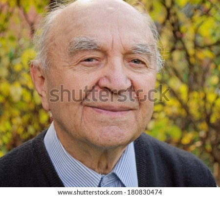 smiling bald old man outdoors in his garden - stock photo