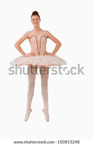 Smiling ballerina standing on her tiptoes against a white background