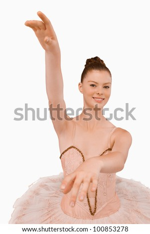 Smiling ballerina with her arms extended against a white background
