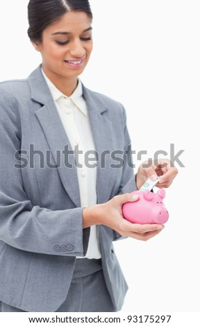 Smiling bank employee putting bank note into piggy bank against a white background