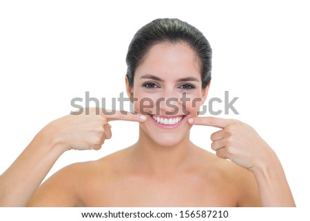 Smiling bare brunette pointing at her mouth on white background