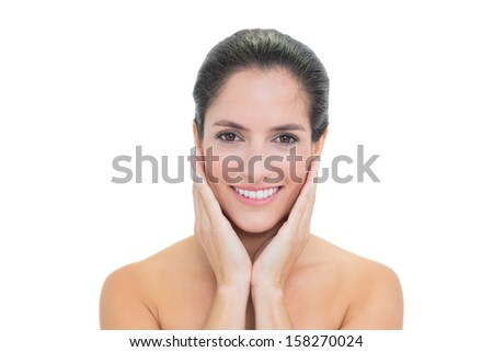 Smiling bare brunette touching her face on white background - stock photo