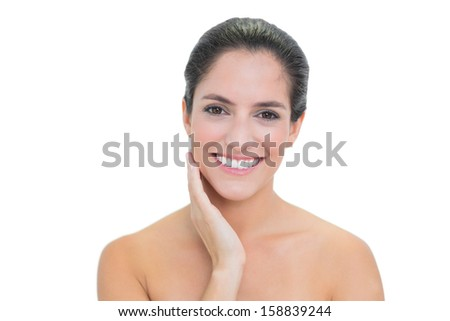 Smiling bare brunette touching her left cheek on white background