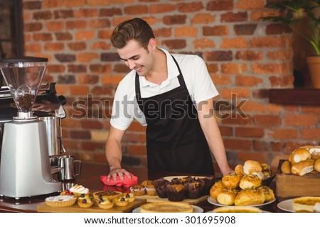 Smiling barista cleaning the counter at coffee shop - stock photo