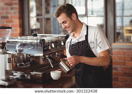 Smiling barista pouring milk into cup at coffee shop - stock photo