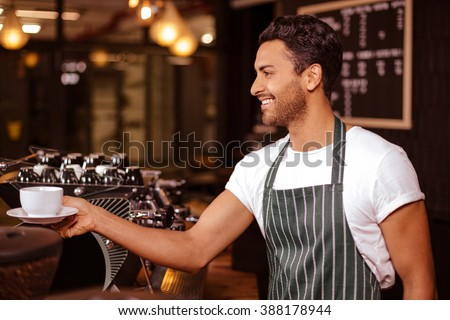 Smiling barista putting espresso on counter in the bar - stock photo