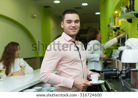 Smiling barista serve coffee and bartenter at background  - stock photo