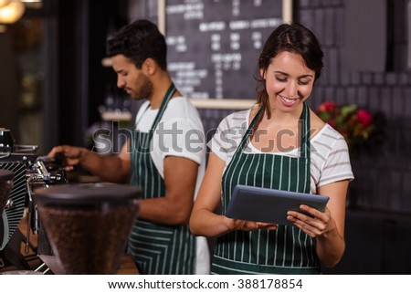 Smiling barista using tablet in the bar