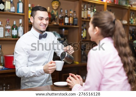 Smiling bartender and barista working at bar. Focus on man - stock photo