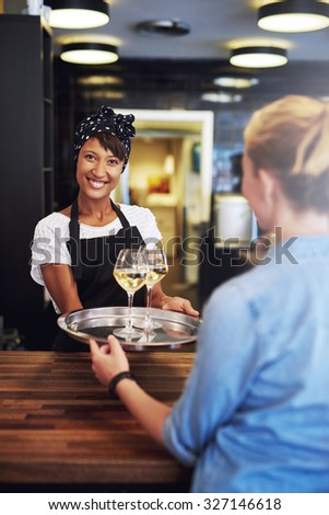 Smiling bartender, waitress or female business owner serving glasses of white wine on a tray to a customer with a lovely friendly smile as she stand behind the wooden counter in a bar - stock photo