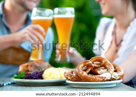 Smiling bavarian couple wearing traditional dress at Oktoberfest - stock photo