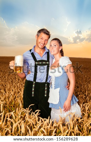 smiling bavarian sunset couple with beer - stock photo