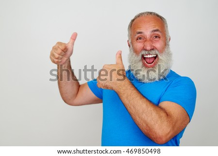 Smiling bearded aged man in bright blue T-shirt is showing two thumbs up gesture isolated against white background