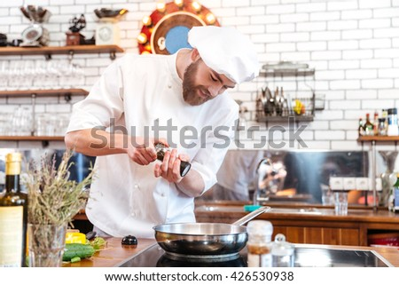 Smiling bearded chef cook standing and cooking in frying pan on the kitchen - stock photo