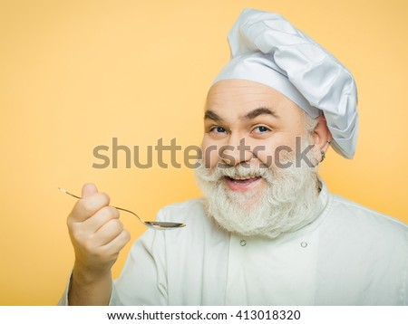 Smiling bearded man cook in hat tasting food with spoon in studio on yellow background, copy space
