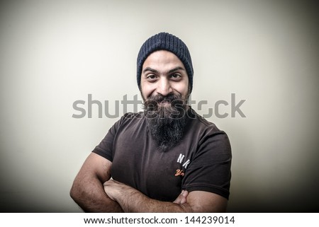 smiling bearded man with cap isolated on gray background - stock photo