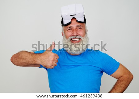 Smiling bearded senior man is cheerful and impressed by virtual reality glasses and showing thumbs up gesture