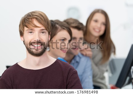 Smiling bearded young businessman posing looking directly at the camera while his colleagues work in the background - stock photo