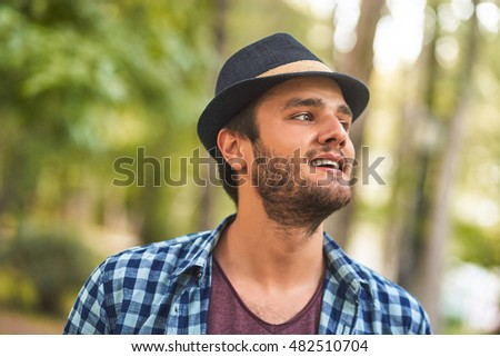 Smiling bearded young man wearing a hat. Outdoors.