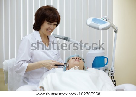 Smiling beautician in beauty salon processes face skin of the patient with the metal massage roller. - stock photo